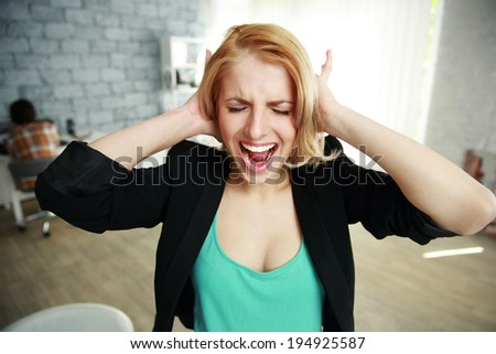 Screaming young woman with closed ears in office - stock photo