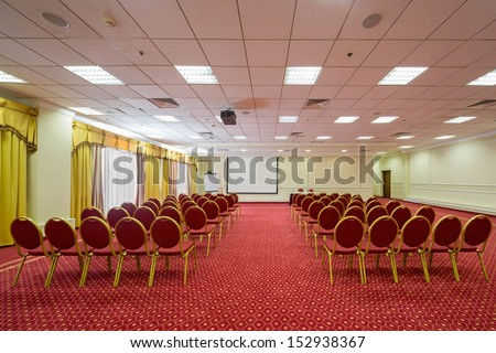 Screen, chairs and projector in empty conference hall with a red carpet on the floor - stock photo