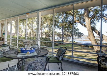 Screen porch with view of trees and waterfront - stock photo