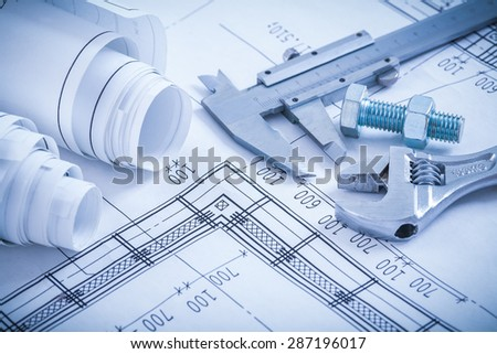Screw bolt with nut adjustable spanner slide caliper rolls of construction plans on blueprint architecture and building concept. - stock photo