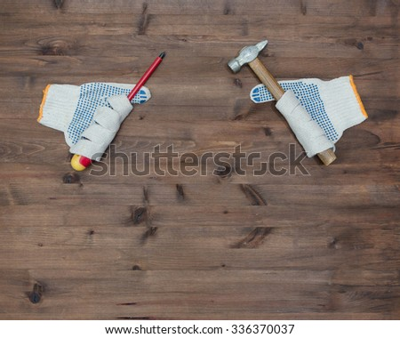 Screwdriver hammer and gloves look like hands on old wooden table - stock photo