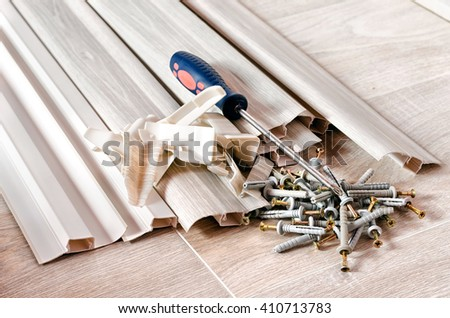 screwdriver, Laminate Flooring and New Baseboard Molding Abstract. - stock photo