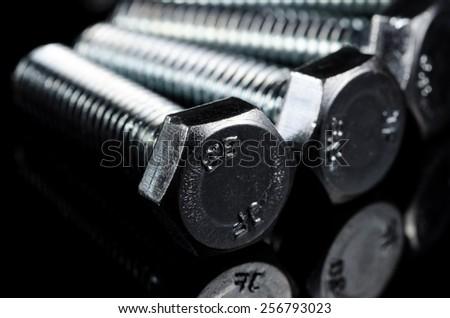Screws ( bolts ) on the black background. Macro shot. - stock photo