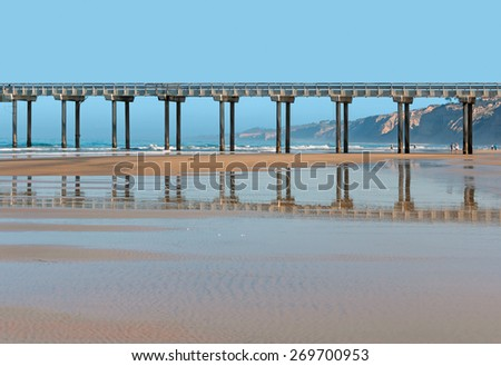 Scripp's pier and reflection in the wet sand. Side view of long concrete structure. People at leisure walking along the shoreline in the background.  - stock photo