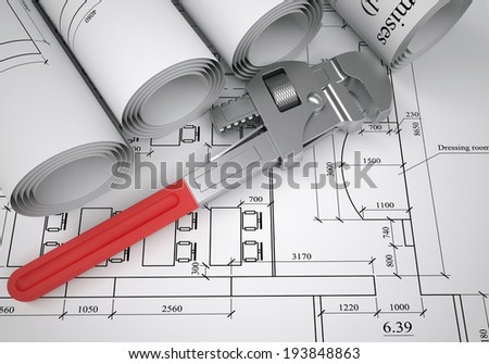 Scrolls of architectural drawings and pipe wrench. The desk worker - stock photo