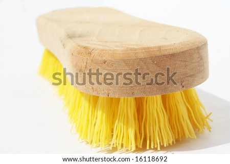 Scrub brush with polyester yellow bristles and wood handle against white background - stock photo