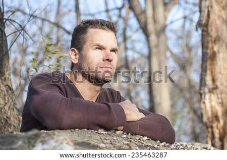 Scruffy handsome Caucasian man with arms crossed leaning over fallen log in thick wooded area stares off into distance in deep thought - stock photo