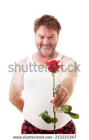 Scruffy looking man in his underwear holding out a single red rose for his sweetheart.  Isolated on white.   - stock photo