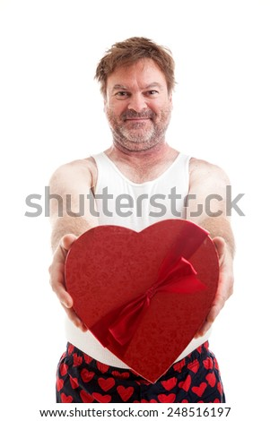Scruffy middle aged man giving you a heart shaped box of candy for Valentines Day.  Isolated on white - stock photo