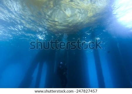 Scuba Diver at underwater Oil Rig Dive Site - stock photo