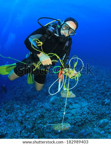 Scuba Diver cleans up trash polluting coral reef - stock photo