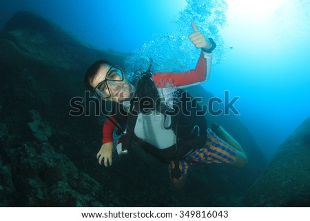 Scuba diver diving explores coral reef in ocean - stock photo