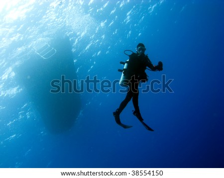 Scuba Diver doing a safety stop on the way back to the Boat - stock photo