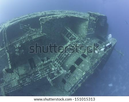 Scuba diver exploring a large sunken underwater shipwreck - stock photo