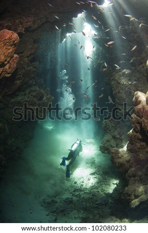 Scuba diver exploring an underwater cave framed in beams of sunlight - stock photo