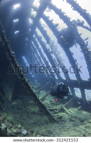 Scuba diver exploring inside a large underwater shipwreck - stock photo