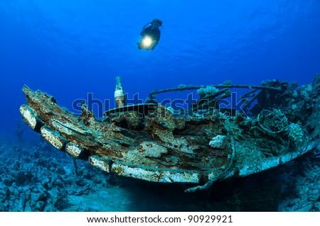 Scuba diver exploring shipwreck - stock photo
