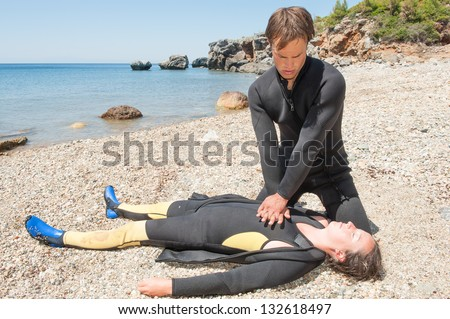 Scuba diver giving CPR to a casualty - stock photo