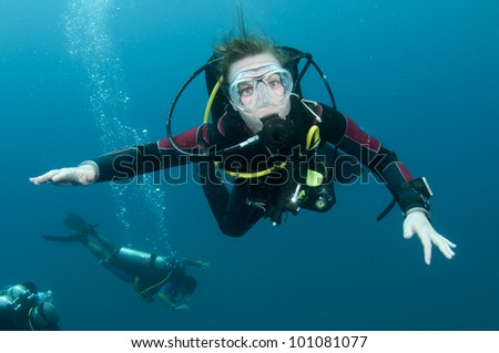 scuba diver looks at camera while swimming in Thailand - stock photo