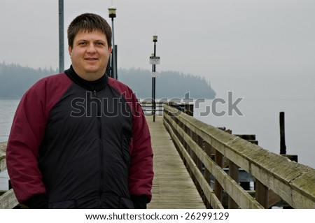 Scuba diver posing on dock - stock photo