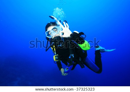 Scuba Diver signals that she is okay - stock photo