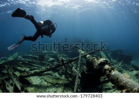 Scuba diver swimming over a Ship wreck - stock photo