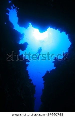 Scuba Divers about to descend into an underwater canyon - stock photo