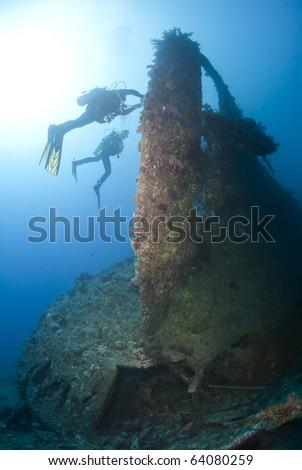 Scuba divers exploring the propellor area of a shipwreck. Dunraven, Beacon rock, Red Sea, Egypt. - stock photo