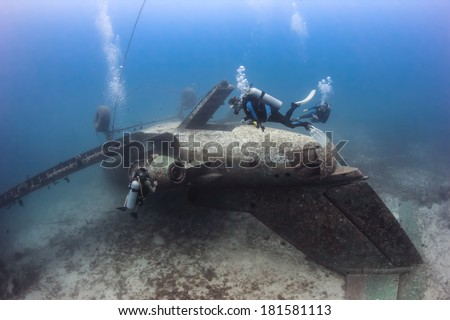 SCUBA divers exploring the upturned fuselage of an underwater aircraft wreck - stock photo