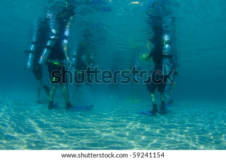 Scuba divers standing in shallow water prior to a beach dive. - stock photo