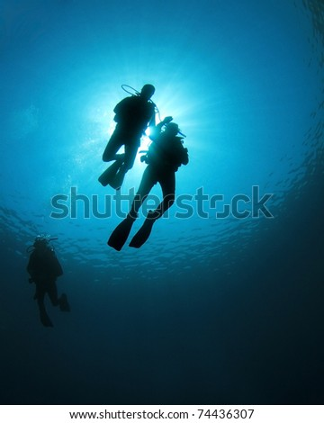 Scuba Divers swim together in blue ocean, silhouette against sunburst - stock photo