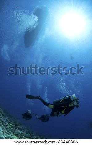 scuba divers with boat in background in the Bahamas - stock photo