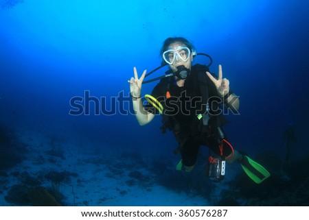 Scuba diving exploring coral reef in Similan Islands Thailand - stock photo