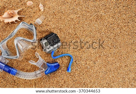 Scuba mask and snorkel on the sand. Action camera and shells. - stock photo