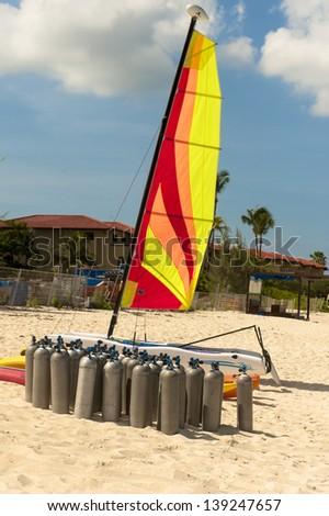 Scuba tanks on the beach beneath a colorful sail - stock photo