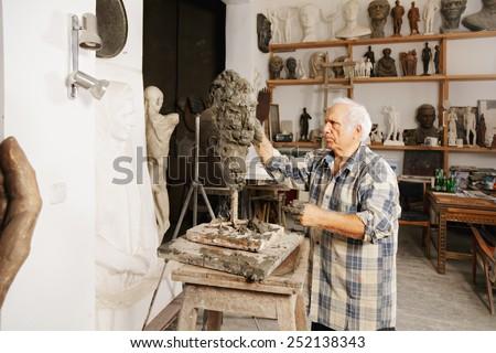 Sculptor creates head in a studio - stock photo