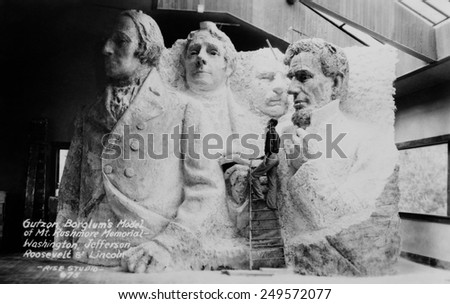 Sculptor Gutzon Borglum (1871-1941), on a ladder with his model of Mt. Rushmore memorial. 1936. - stock photo