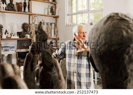 Sculptor in studio raising palm while looking sideways - stock photo