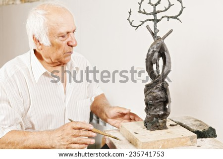Sculptor looking at his work in a workshop - stock photo