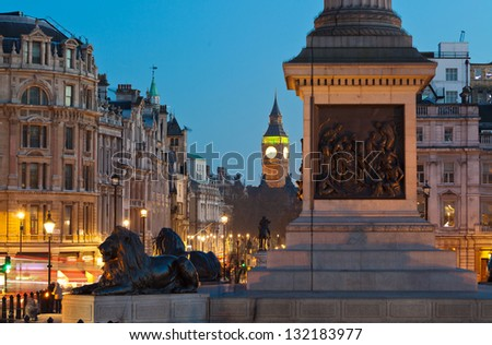 Sculpture lying lions at Nelson's Column pedestal in Trafalgar Square. Whitehall Street and Big Ben in the distance. Twilight - stock photo