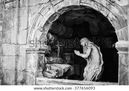Sculpture of an old man praying  - stock photo
