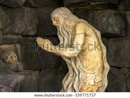 sculpture of an old man praying skull stone - stock photo
