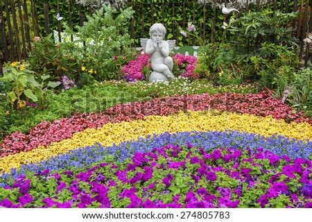 Sculpture of angel in ornamental garden - stock photo