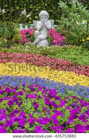Sculpture of angel in ornamental garden - stock photo