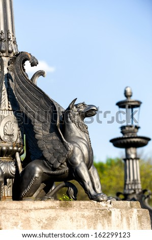 sculpture of griffin on stone pedestal in autumn sunny day - stock photo