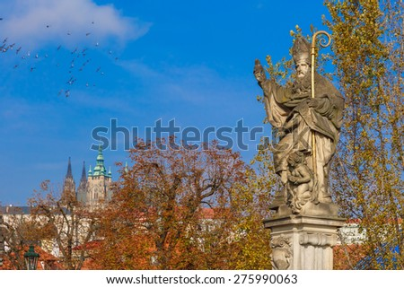 Sculpture of St. Augustine with a burning heart in hand trampling heretical books on Charles Bridge in Prague, Czech Republic - stock photo