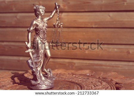 sculpture of themis, femida or justice goddess on wood lining copy space background - stock photo