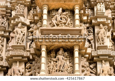 Sculptured surface of famous indian temple of Khajuraho with Hindu gods. UNESCO Heritage site, built between 950 and 1150 in India, belong to two different religions - Hinduism and Jainism. - stock photo