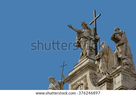 Sculptures of Jesus among saints and apostles at the top of Saint John Cathedral in Roma - stock photo