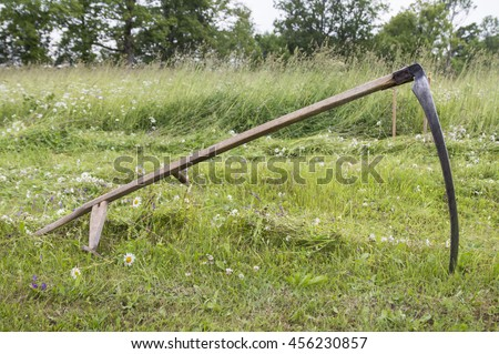 Scythe with grass - stock photo